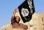"""A militant Islamist fighter waving a flag, cheers as he takes part in a military parade along the streets of Syria's northern Raqqa province June 30, 2014. The fighters held the parade to celebrate their declaration of an Islamic """"caliphate"""" after the group captured territory in neighbouring Iraq, a monitoring service said. The Islamic State, an al Qaeda offshoot previously known as Islamic State in Iraq and the Levant (ISIL), posted pictures online on Sunday of people waving black flags from cars and holding guns in the air, the SITE monitoring service said. Picture taken June 30, 2014.  REUTERS/Stringer (SYRIA - Tags: POLITICS CIVIL UNREST CONFLICT) - RTR3WKMT"""